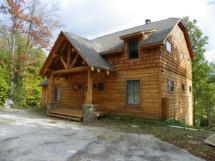 Custom rustic log truss and entryway and log siding by Adirondack LogWorks