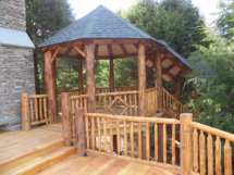 Custom rustic log gazebo with log railings, stairs, trusses, posts, and twig woodwork by Adirondack LogWorks