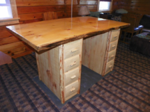 Custom rustic log kitchen island with log trim and live-edge counter top by Adirondack LogWorks