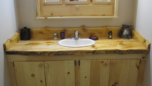 Custom rustic log vanity with live-edge counter top by Adirondack LogWorks
