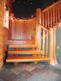 Custom rustic log stairs and log railings in a log home by Adirondack LogWorks