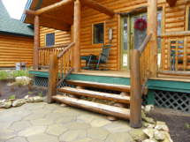 Custom rustic log stairs on the front of a log home by Adirondack LogWorks