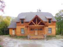 Custom rustic log truss and entryway on a log home by Adirondack LogWorks