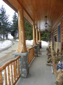 Custom rustic log entryway and log railings on a log home by Adirondack LogWorks