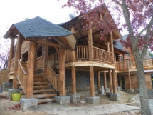 Custom rustic log stairs, railings, posts, and truss woodwork at a log home by Adirondack LogWorks