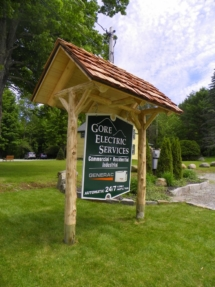 Custom-made rustic log sign holder and log posts with cedar shake roof for Gore Electric by Adirondack LogWorks