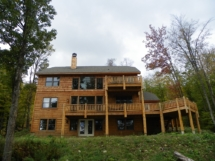 Custom rustic log railings, posts, and siding by Adirondack LogWorks