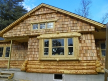 Custom rustic log siding and log trim woodwork on a log home by Adirondack LogWorks