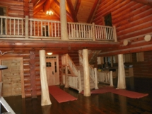 Custom rustic log posts, stairs, and railings at a log home by Adirondack LogWorks