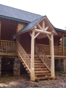 Custom log entryway with rustic truss, railing, and stair woodwork by Adirondack LogWorks