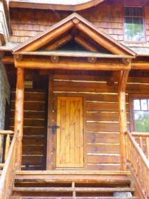 Custom rustic log truss, entryway, stairs, railings, and siding woodwork by Adirondack LogWorks