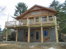 Custom rustic log entryway, posts, siding, and railings by Adirondack LogWorks
