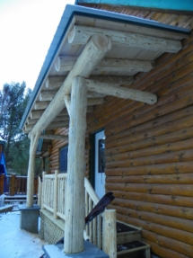 Custom rustic log truss, entryway, and railing woodwork at a log home by Adirondack LogWorks