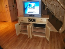Custom-made rustic log entertainment unit with doors, drawers, twig woodwork, and log trim by Adirondack LogWorks