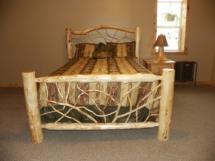 Custom rustic log bed with twig headboard and twig footboard by Adirondack LogWorks