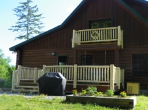 Custom rustic log stairs and railings with diamond twig inlay at a log home by Adirondack LogWorks