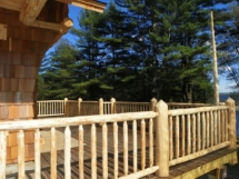 Custom rustic log railings at a log home by Adirondack LogWorks