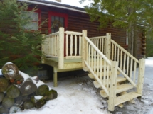 Custom rustic log stairs and railings on a log home porch by Adirondack LogWorks