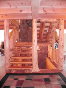 Custom rustic log stairs and flair-based log post woodwork by Adirondack LogWorks