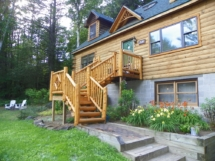 Custom log stairs and railings with diamond twig inlay at a log home by Adirondack LogWorks