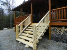 Custom rustic log stairs and railings on a log home by Adirondack LogWorks
