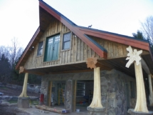 Custom log truss and entryway with rustic flair woodwork by Adirondack LogWorks