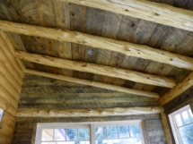 Custom rustic log trusses in a log home breakfast nook by Adirondack LogWorks