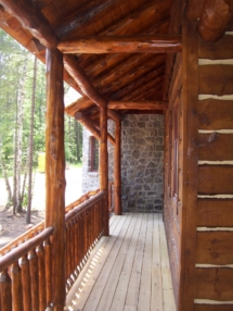 Custom log home truss, entryway, siding, and railing woodwork by Adirondack LogWorks